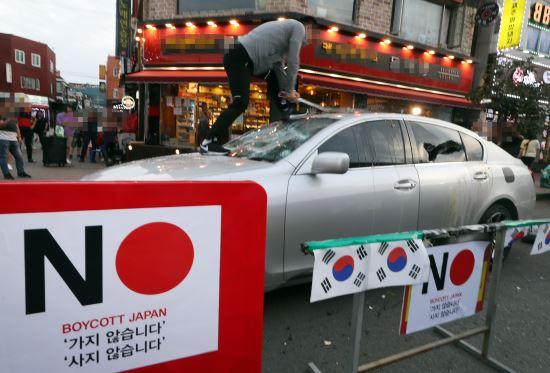 7月23日,韩国仁川,有民众当街砸掉一辆雷克萨斯。(韩联社)