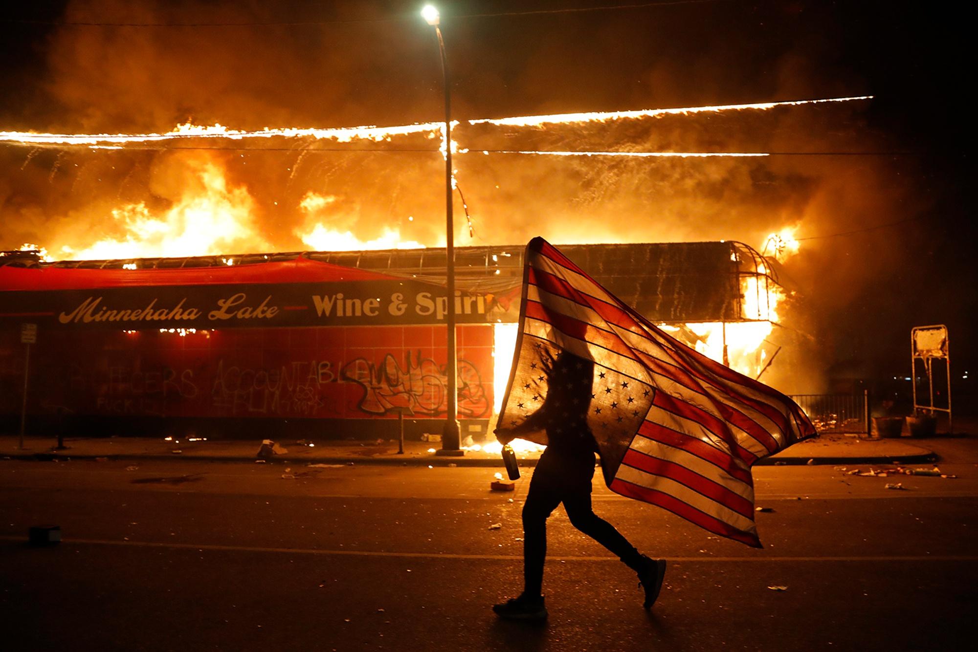 28日,明尼阿波利斯市,一名抗议者倒拿美国国旗奔跑。(美联社)