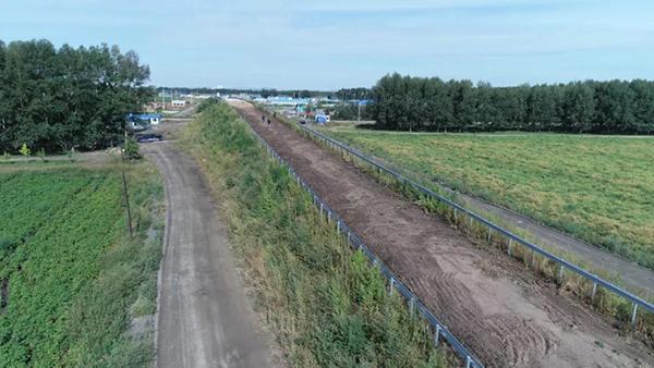 平改立工程K11公里道口,已建成的沙土桥梁。可以看到下桥的辅路和桥梁之间,完全没有预留转弯的空间。(8月28日 航拍图)达日罕 摄