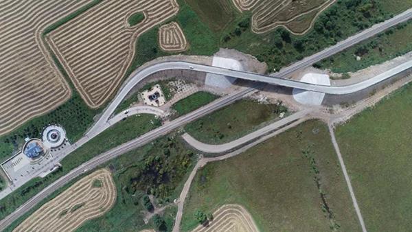 """平改立工程乌尔其汗煤田森林检查站附近,可以看""""S""""型的桥梁如果弯道曲度适当,应当穿过林业局的检查站。(8月28日航拍图)达日罕 摄"""