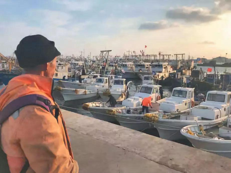 ▲11月15日清晨,渔民李国来到岸边查看他的小船,天气好的时候就出去打打鱼。