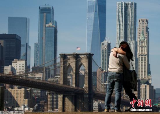 一对情侣相拥在布鲁克林大桥旁。