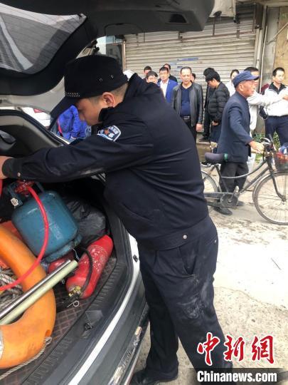 民警将男子手中的煤气罐收好,照片显示其大腿一侧裤子破损。永嘉公安供图