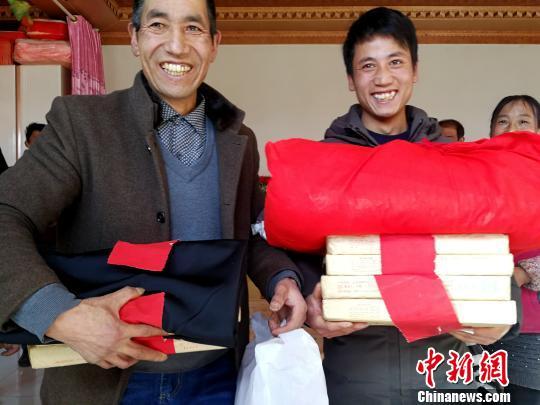 图为李吉胜(左)和幼儿子准备向女方送彩礼。 张增福 摄