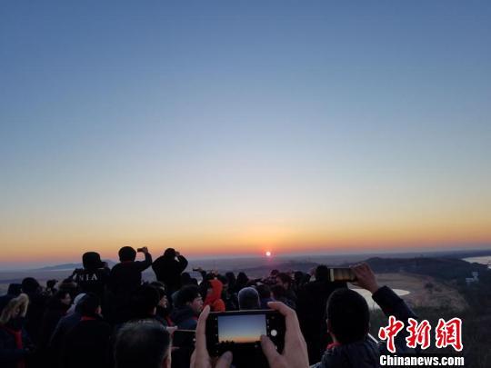 6时46分许,新年的第一缕阳光冲破天际,在珲春龙虎阁上的三国民众及海内外游客纷纷拍照留下这一美好瞬间。 张瑶 摄