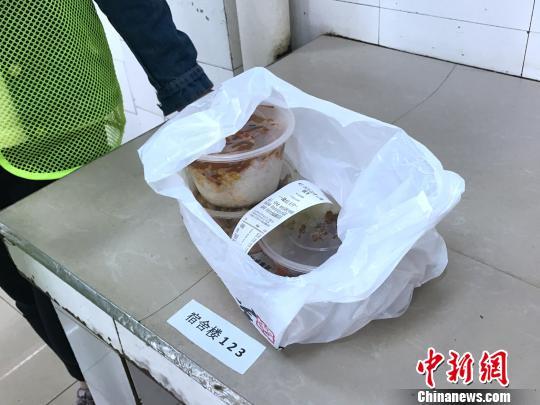 图为送餐的学生按宿舍地址分配餐品。 张一辰 摄