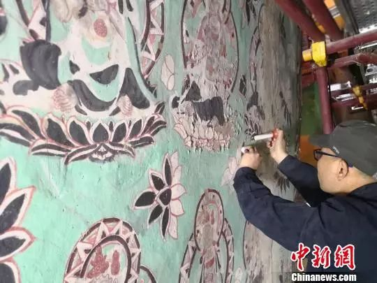资料图:2018年5月16日,壁画修复师修复莫高窟130窟起甲壁画。 南如卓玛 摄