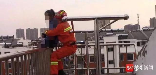 消防员一个箭步上前 拦腰从后面将跳楼女生抱下。 截屏图