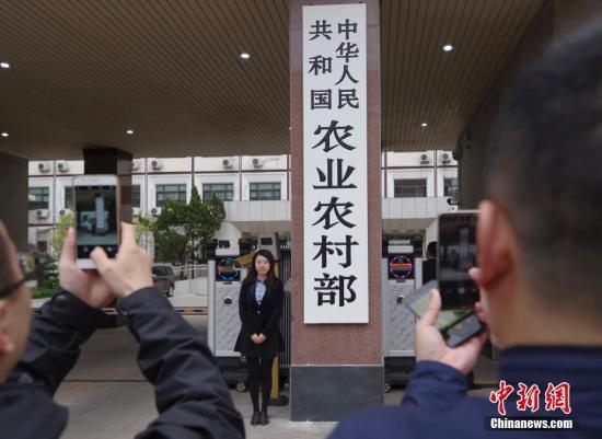 4月3日,新组建的中华人民共和国农业农村部在北京正式挂牌,民众争相与新牌合影。 中新社记者 贾天勇 摄