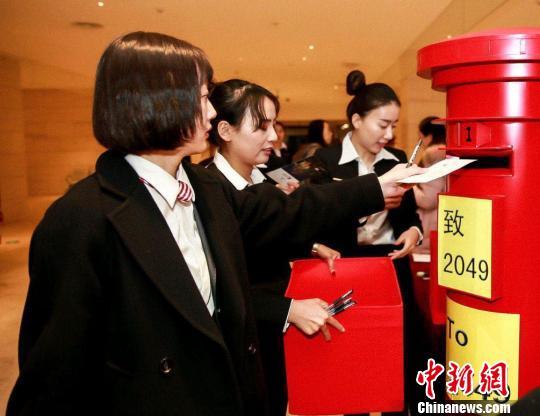 与会人员在卡片上写下对中国金融的期冀与歌颂,投放至寄语箱密封保存,30年后将举走开启仪式,谨以此致敬2049。北京市金融界供图 摄