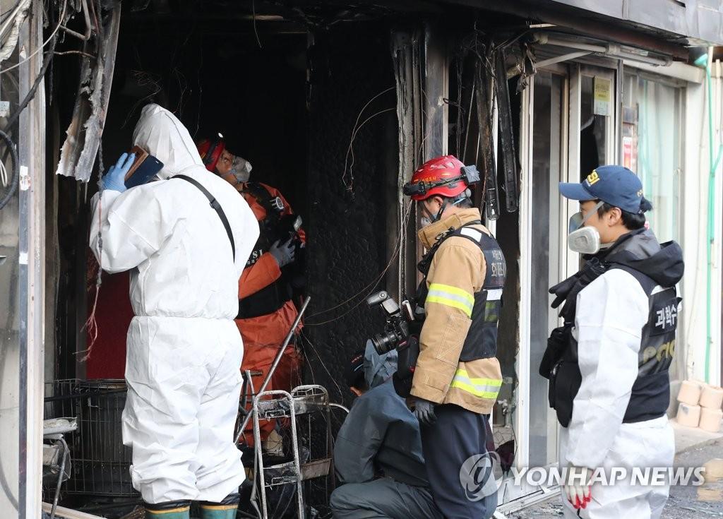 22日下昼,调查人员正在进入火灾现场。(韩联社)