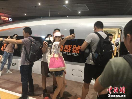 9月23日,广深港高铁香港段正式开通运营。民众在车前自拍。 中新社发 张茜茜 摄