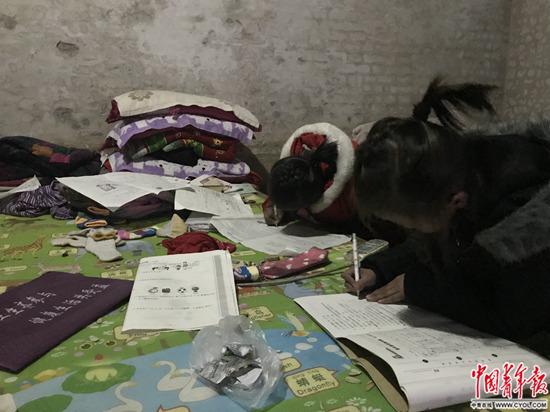 1月4日,张欢张圆姐妹正趴在床上写作业。中国青年报·中青在线记者孙庆玲/摄