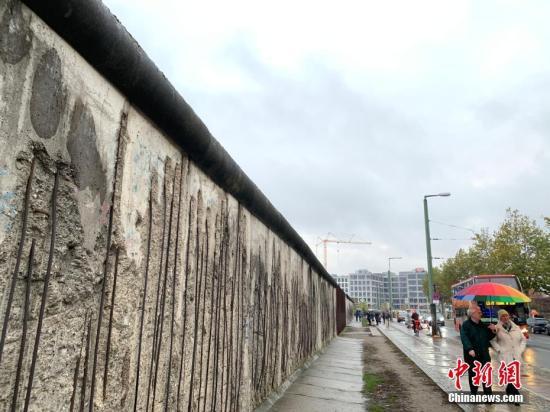 资料图:11月9日是柏林墙倒塌30周年纪念日,当天在德国首都柏林等地举行了多种纪念活动。图为人们当天下午经过柏林墙遗址纪念公园内保留的一段柏林墙。中新社记者 彭大伟 摄