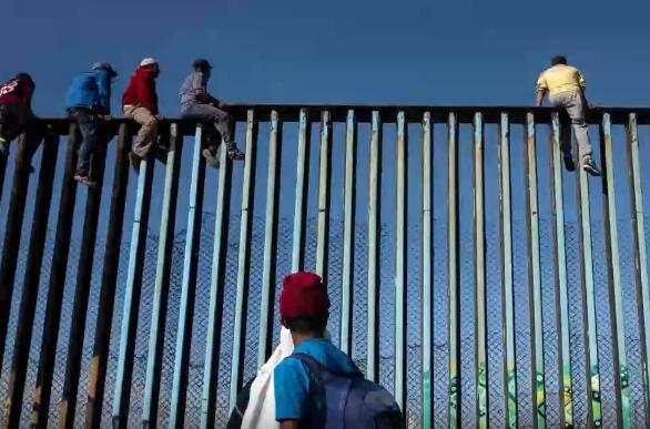 抵达美墨边境的侨民爬上边境围栏(视频截图)