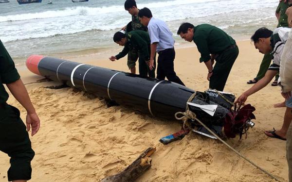 身穿越南军绿色服装的人员在检查该物体。