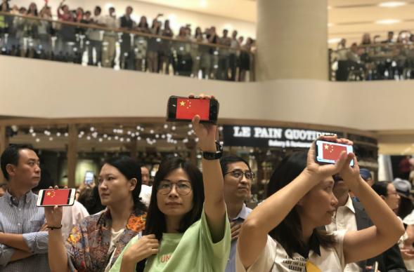 """大批市民在远古广场中庭""""快闪""""唱国歌。(来源:橙讯休)"""
