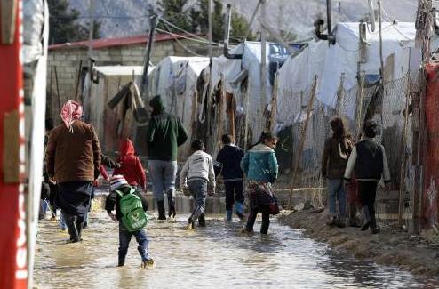 资料图片:1月17日,在黎巴嫩贝卡谷地的一处叙利亚难民营,人们在积水中行走。(法新社)
