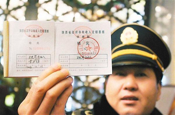 执法人员展现首张罚单。西安日报记者 李明 演习生 徐楠图