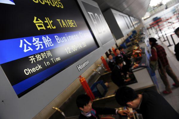 2008年12月26日,旅客在青岛流亭国际机场办理登机手续。当日,青岛至台湾空中客运直航正式开通。新华社记者李紫恒摄