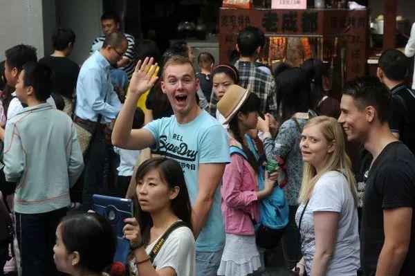 ▲外国游客在成都宽窄幼径游戏。