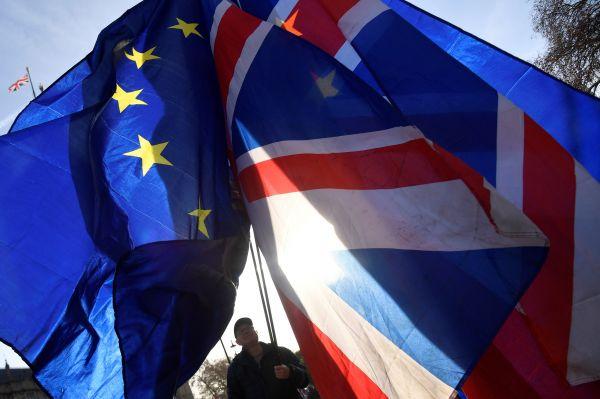 逆脱欧抗议者17日在位于伦敦的议会大厦表挥舞欧盟旗帜和英国国旗(路透社)