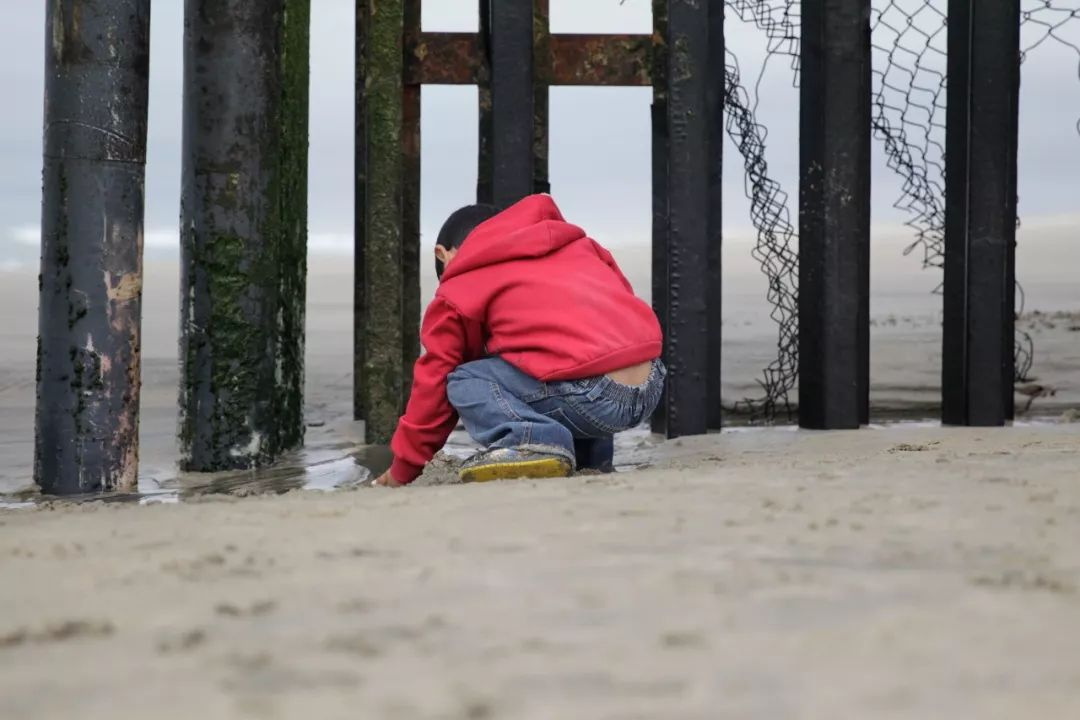 2017年2月6日,在墨西哥蒂华纳海滩,别名儿童蹲在美墨边境墙前玩沙子。(新华社记者淡航摄)