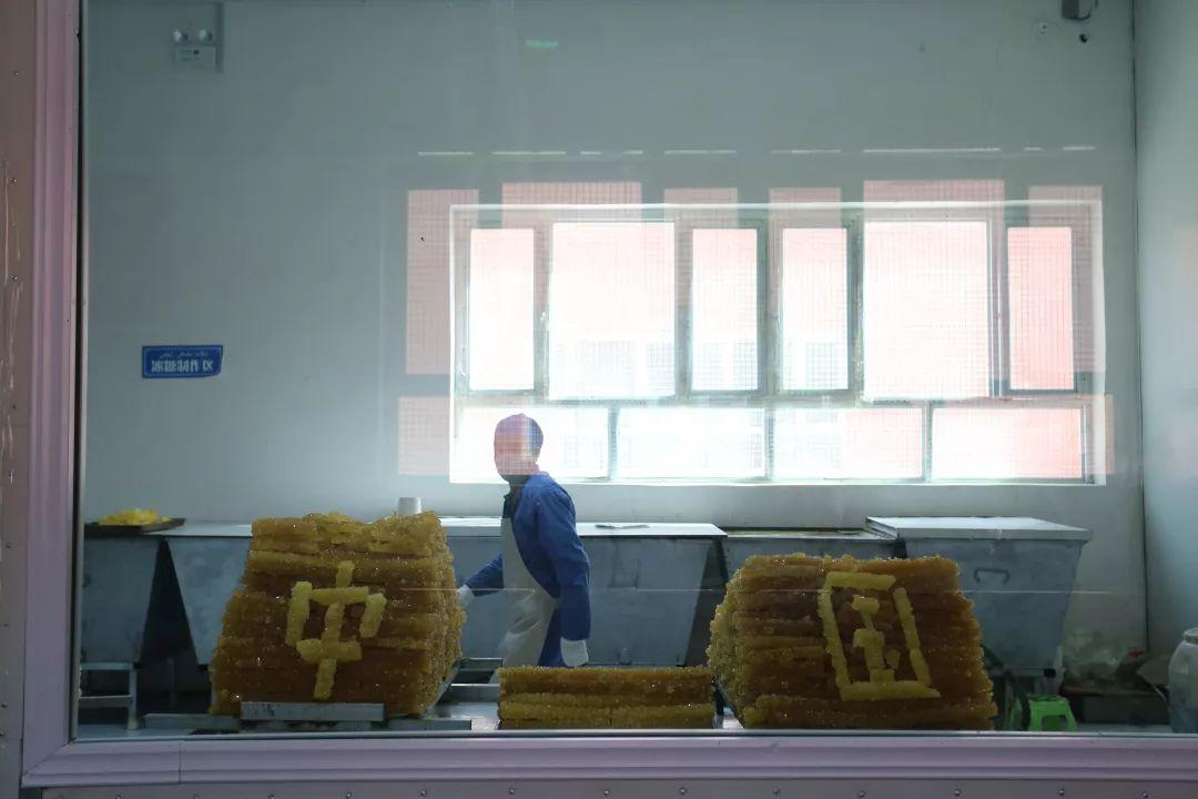 """于田县做事技术哺育培训中心食品厂的职工把冰糖拼成""""中国""""字样。摄影:范凌志"""