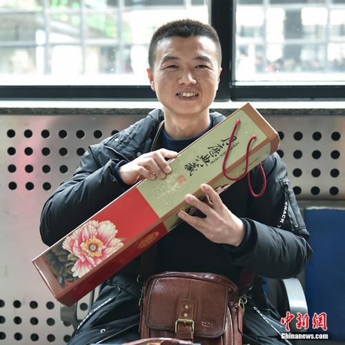 陈先生给家人带回一份装裱精致的牡丹挂历。中新网记者 翟璐 摄