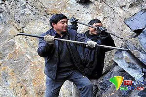 王光国带领村民在悬崖绝壁上修路。资料图