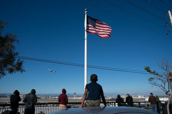 3月13日,在美国洛杉矶国际机场外,市民观看飞机起降。(新华社)