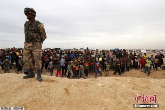 原料图:当地时间2016年5月4日,约旦始都安曼东部 Hadalat区,大批叙利亚难民在约旦叙利亚边境期待进入约旦。图为约旦叙利亚边境别名约旦士兵在放哨。