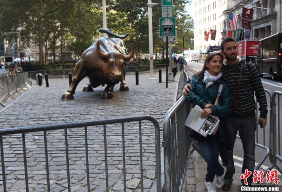 资料图:民众在华尔街铜牛前合影。中新社发 阮煜琳 摄
