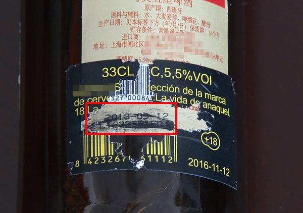 撕開啤酒瓶上的一層標簽,里頭的生產日期是2013年的。視頻截圖
