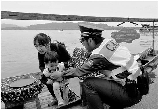 西湖水域工作人员帮助母子二人下船。 钱江晚报 图