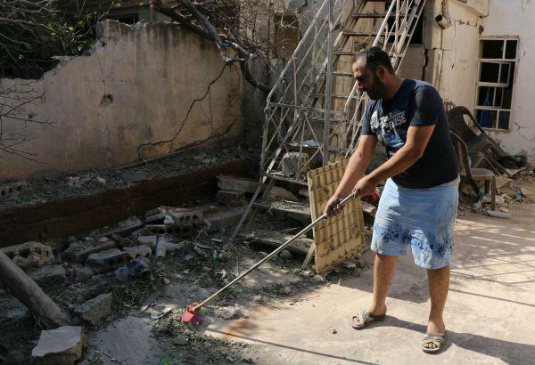 10月12日,叙利亚哈塞克省卡米什利,一名男子在清扫炮击后留下的碎石瓦砾。(新华社发)