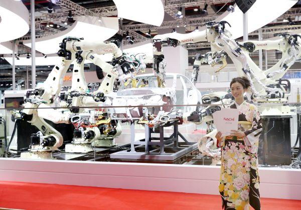 11月5日,一名那智不二越公司的工作人员站在用于汽车制造的焊接机器人展示台前。 新华社记者方喆 摄
