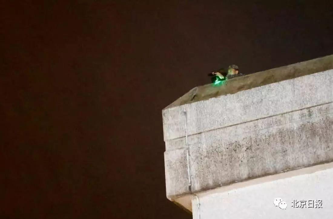 一名军人在军营楼顶,手持摄影机。图片来源:香港卫视