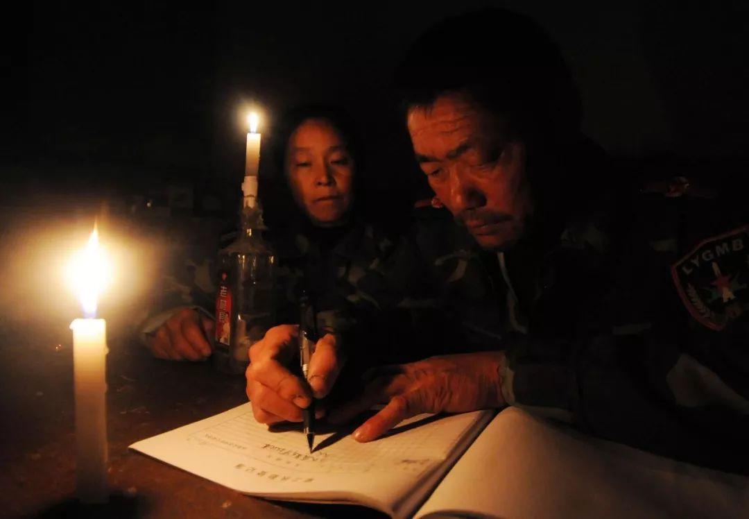 王继才夫妇在烛光下写每天都要记录的巡岛日志(2011年11月1日摄)。新华社发(沈鹏 摄)