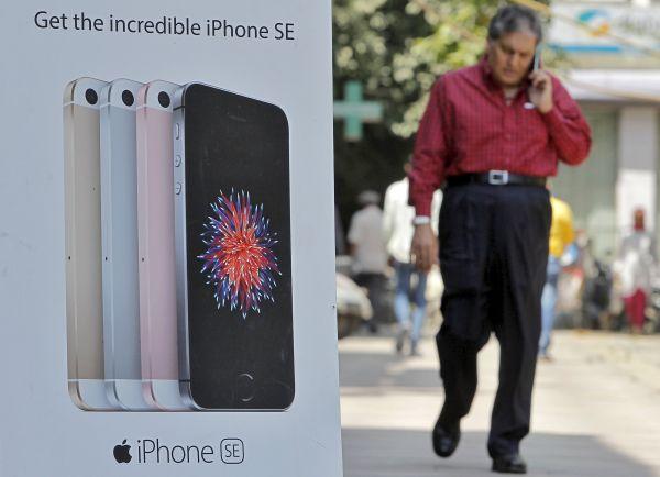资料图片:印度新德里,一名男子走过苹果手机广告牌。(新华社/路透)