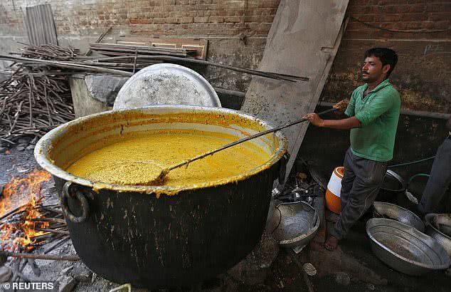 印度民众正在熬煮咖喱。(图源:路透社)