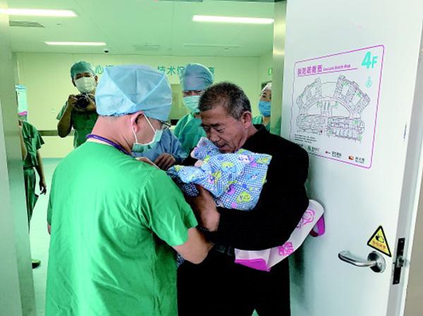 25日,黄师长从医外走中接过女婴。 齐鲁晚报 图