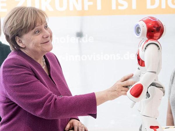 4月默克尔在出席运动时与机器人NAO搞怪互动 图自 德国斯图添特新闻