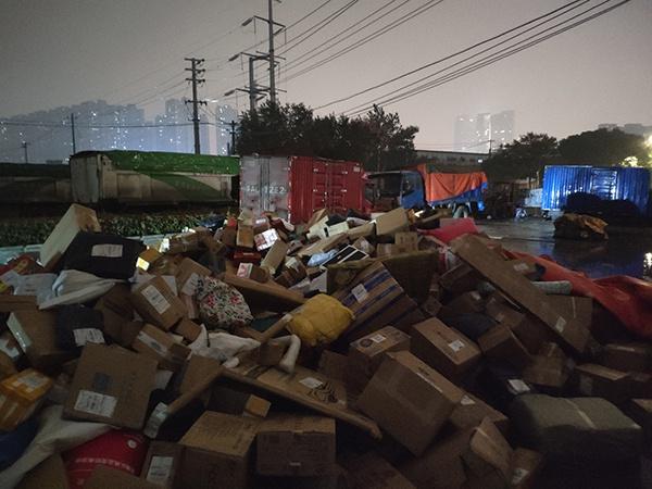 11月17日,百世快递大量包裹被堆放在露天工地。