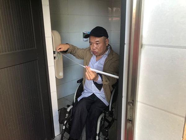 郭兵对无障碍厕所门进行测量。