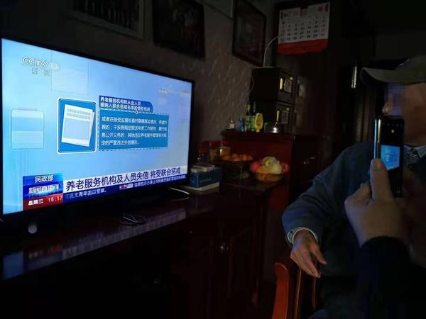 受害老人在爱之心养老公寓内看电视。