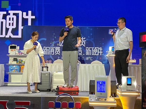 松江区副区长陈晓军(右一)在带货智能跟屁虫90分行李箱。