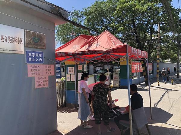 北京某小区外,执勤人员严守大门。澎湃新闻记者 汤琪 图