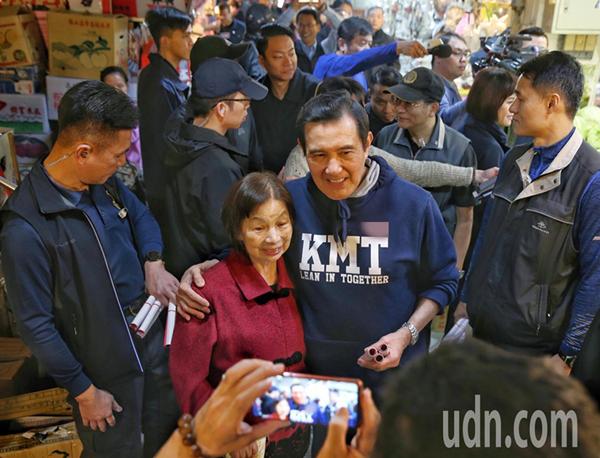 马英九(右)今天到兴隆市场买菜,有热情粉丝上前要求跟他合照。(图片来源:台湾《联合报》)