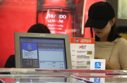 图为在韩国首尔一家免税店,消费者在柜台前付款。新华社